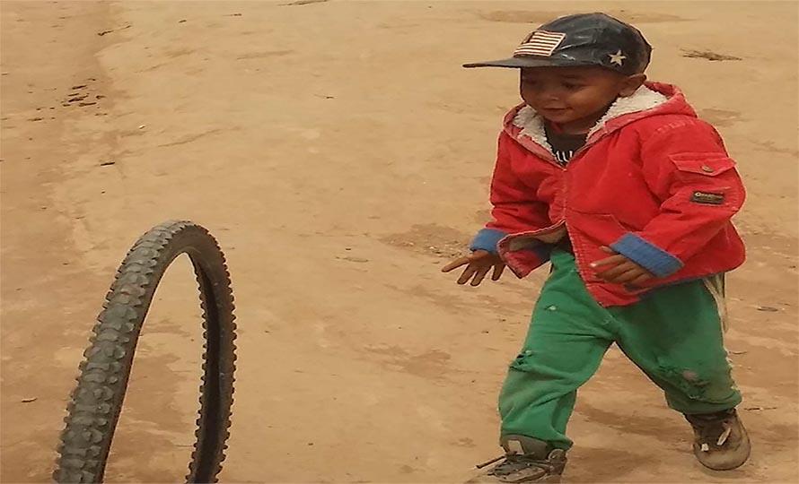 enfant joue avec un pneu